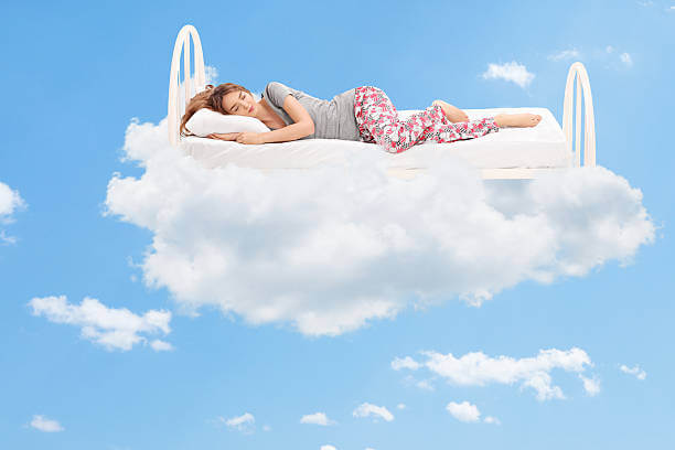 woman-sleeping-on-a-comfortable-bed-in-the-clouds-picture-id473712814